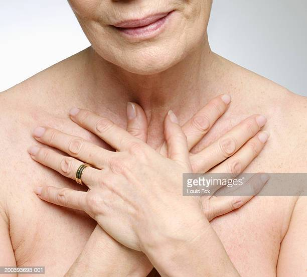 Senior woman with hands crossed on chest, close-up
