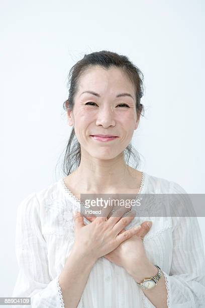 Senior woman with hands on chest, smiling