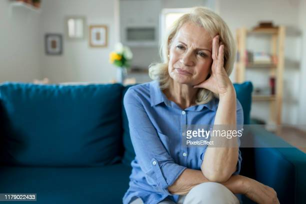 senior woman with headache - 60 69 years stock pictures, royalty-free photos & images