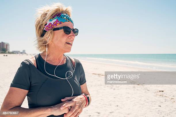 """senior woman with headphones ready to do workout on beach. - """"martine doucet"""" or martinedoucet stock pictures, royalty-free photos & images"""