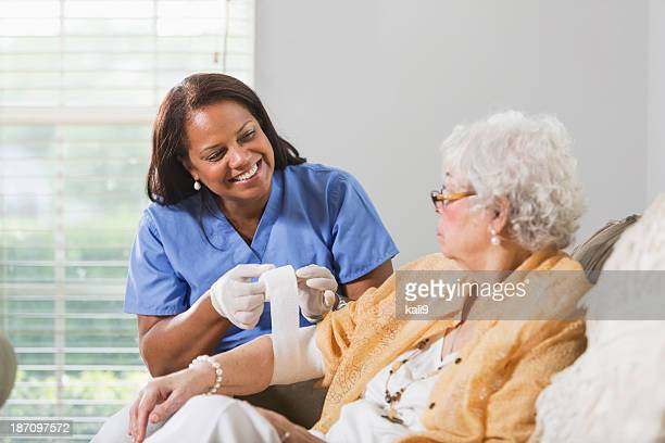 senior woman with healthcare worker - bandage stock photos and pictures