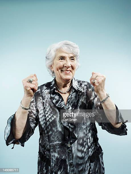 A senior woman with her arms raised in celebration