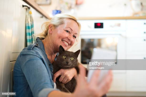 senior woman with her cat at home relaxing - puss pics stock photos and pictures