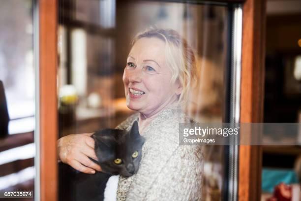 Ältere Frau mit ihrer Katze zu Hause entspannen