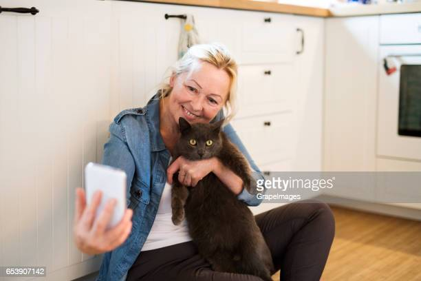 senior woman with her cat at home taking selfie. - puss pics stock photos and pictures