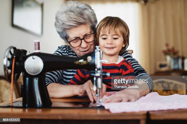 Senior woman with her grandson working on a sewing machine