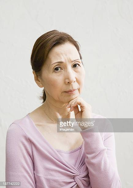 Senior woman with her hand under chin