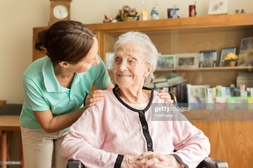 Senior woman with home caregiver : Stock Photo