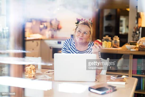 Senior woman with laptop at the kitchen table, eating apple