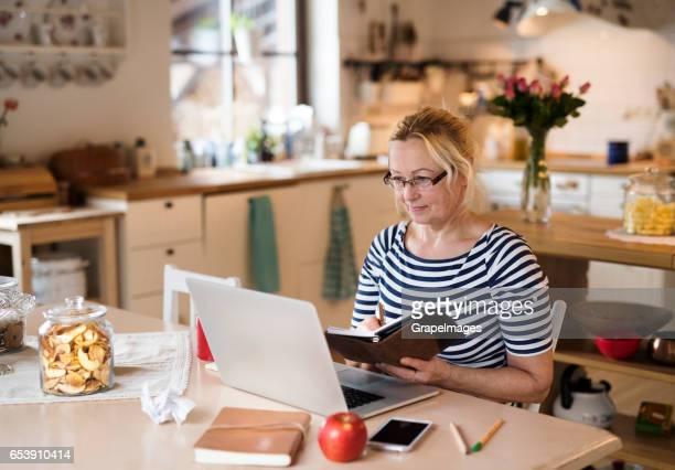 Ältere Frau mit Laptop, arbeiten am Küchentisch