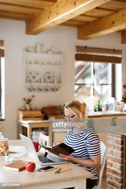 Senior woman with laptop, working at the kitchen table
