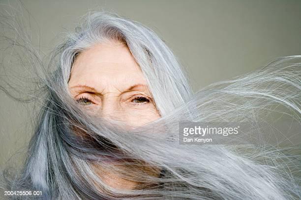 senior woman with long hair blowing across face, portrait, close-up - cabelo grisalho - fotografias e filmes do acervo