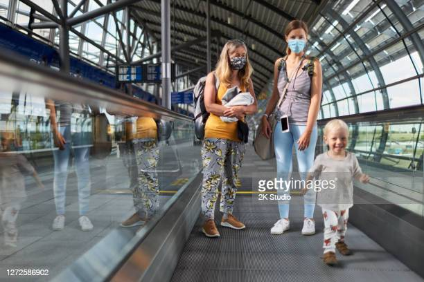 a senior woman with long hair stands with her blond middle-aged daughter and a blond toddler on the rolling sidewalk at the airport wearing surgical masks or face masks before they go on vacation - toddler at airport stock pictures, royalty-free photos & images