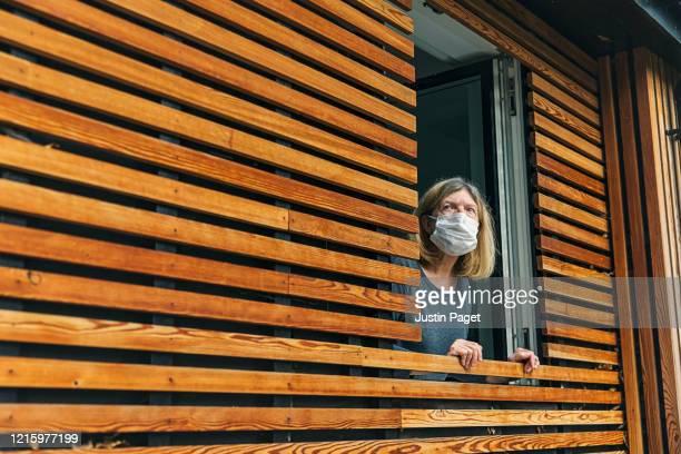 senior woman with mask looking out of window - munskydd ensam bildbanksfoton och bilder