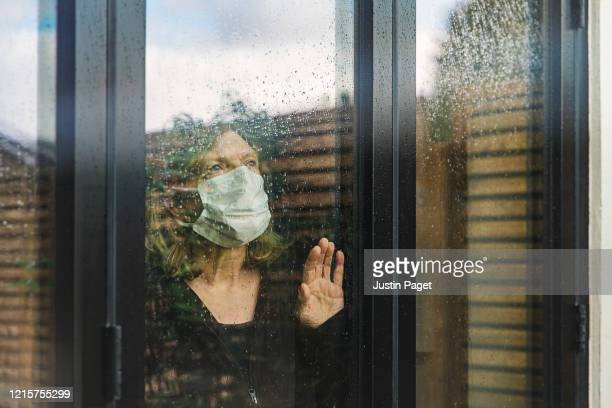 senior woman with mask looking through window - solitude stock pictures, royalty-free photos & images