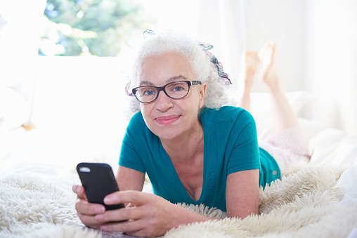 senior woman with mobile phone lying on bed - gettyimageskorea