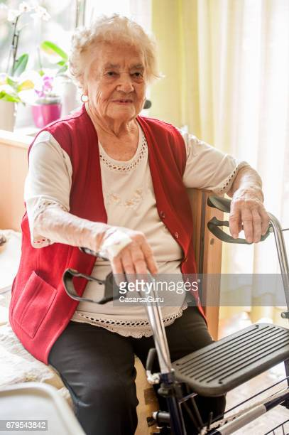 Senior Woman With Mobility Walker Sitting On Her Bed In The Retirement Community