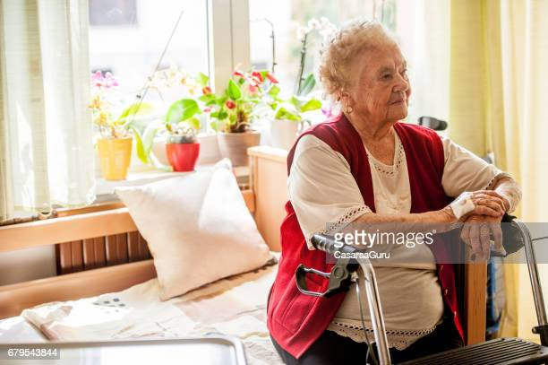 senior woman with mobility walker sitting on her bed in the retirement community - residential care stock photos and pictures