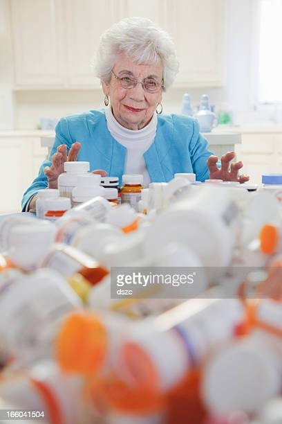 senior woman with mountain of pill bottles - female mound stock pictures, royalty-free photos & images