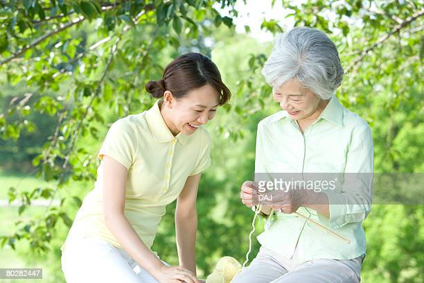 Senior woman with nurse smiling and knitting