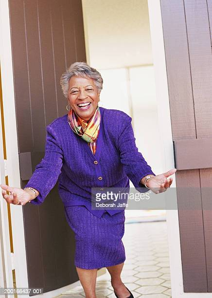 Senior woman with open arms in doorway, smiling, portrait