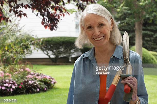 Senior woman with pair of gardening clippers