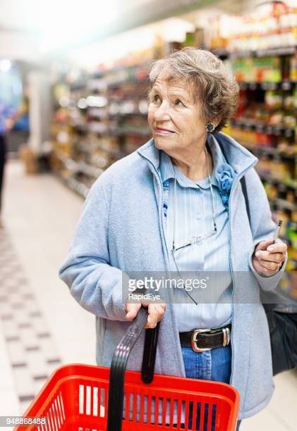 senior woman with shopping basket in supermarket - one senior woman only stock pictures, royalty-free photos & images