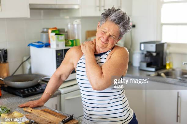 senior woman with shoulder pain - shoulder stock pictures, royalty-free photos & images