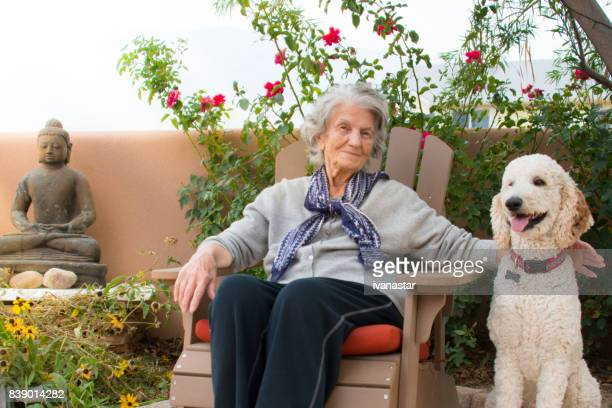 Senior Woman with Standard Poodle in Backyard