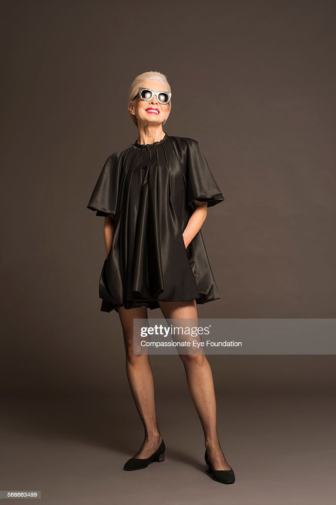 Senior woman with sunglasses and black satin dress : Stock Photo
