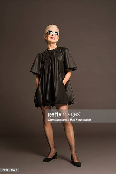 senior woman with sunglasses and black satin dress - satin dress stock pictures, royalty-free photos & images