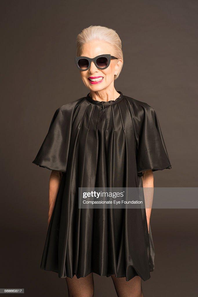 Senior woman with sunglasses and black satin dress : Stock Photo