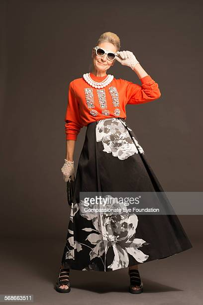 senior woman with sunglasses and stylish clothes - floral pattern skirt stock pictures, royalty-free photos & images