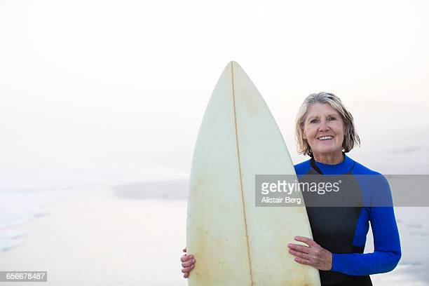 senior woman with surf board - 65 69 jahre stock-fotos und bilder