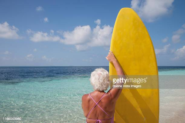 senior woman with surfboard - male maldives stock pictures, royalty-free photos & images