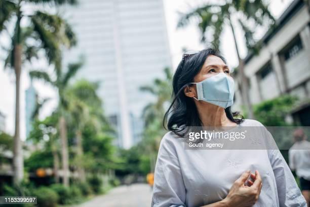 femme aînée avec le masque chirurgical dans la rue - masque de chirurgien photos et images de collection