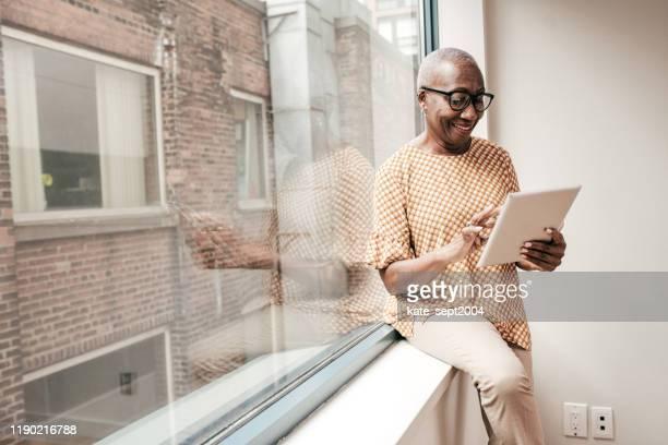mulher sênior com tabuleta perto da janela - flexibilidade - fotografias e filmes do acervo