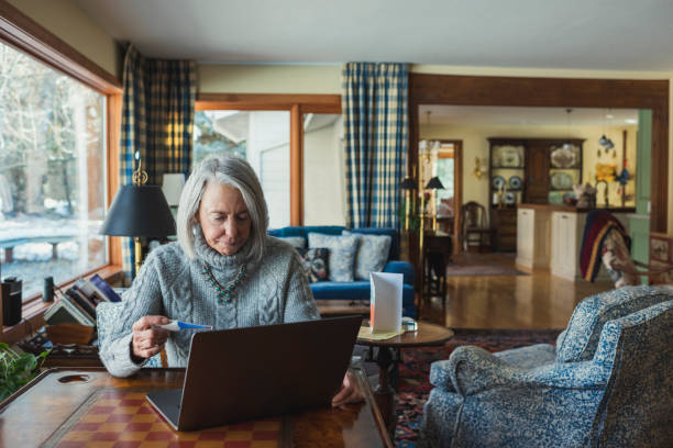 Senior woman with thermometer and laptop at home