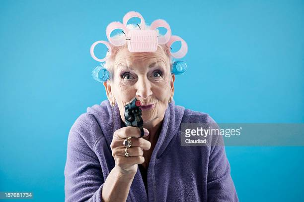 senior woman with toy pistol - very ugly women stock photos and pictures