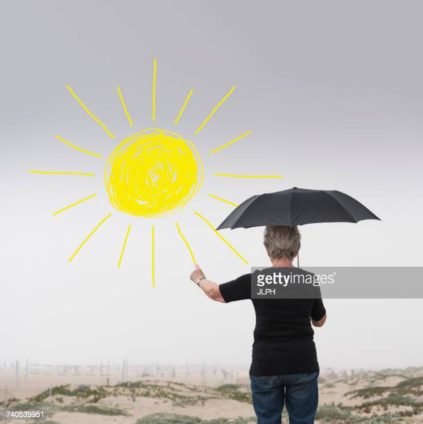 Senior woman with umbrella drawing sun in air