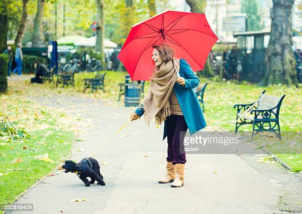 Senior woman with umbrella walking a dog in a park