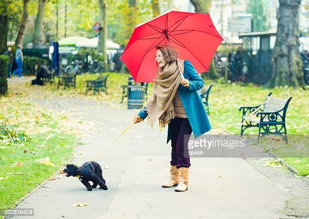 Senior Frau mit Regenschirm walking im park mit Hund