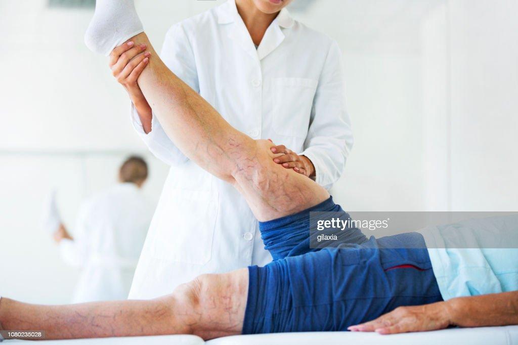 Ältere Frau mit Krampfadern Beinvenen in Arztpraxis. : Stock-Foto