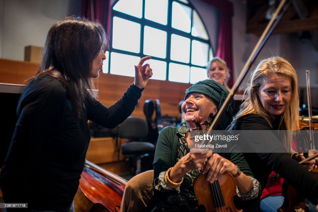 Senior woman with violin at orchestra rehearsal : Stock Photo