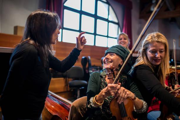 Senior woman with violin at orchestra rehearsal