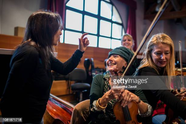 Senior woman with violin at orchestra rehearsal