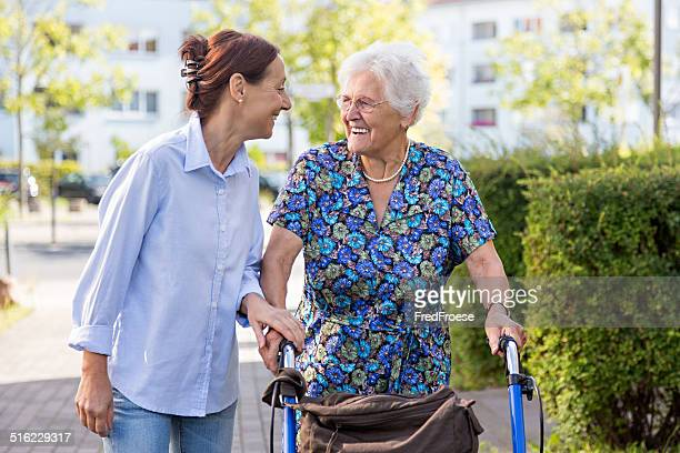 Senior woman with walker and caregiver go walking outdoors