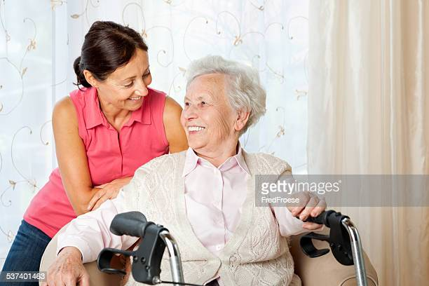 Senior woman with walker and carer at home