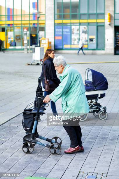 senior woman with walker and young mom - generation gap stock photos and pictures