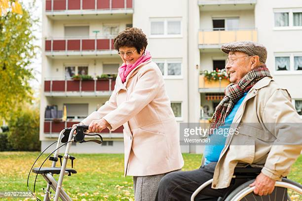 Senior woman with wheeled walker and senior man in wheelchair outdoors in autumn